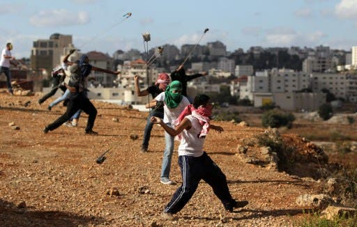Palestinian protesters hurl rocks at Israeli soldiers during clashes in Betunia near the West Bank city of Ramallah on October 4, 2013. The Palestinian and Israeli delegations locked horns at the IPU meeting in Geneva on Wednesday. (AFP)