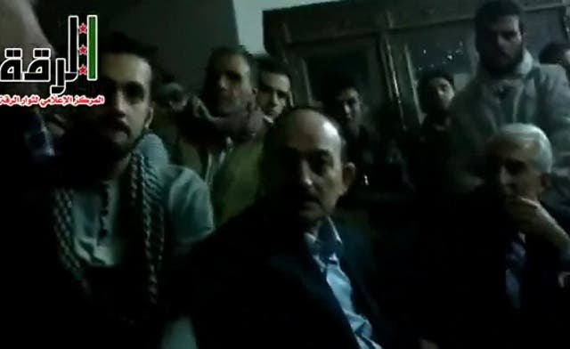 Syrian rebels appear in this YouTube video gathered around two men, one of them identified as Raqqa governor Hussein Jalali. (Al Arabiya)