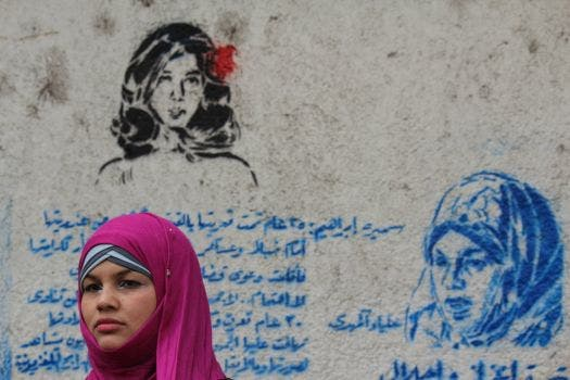 Samira Ibrahim standing next to a graffiti mural that honors her plight. (Image source: