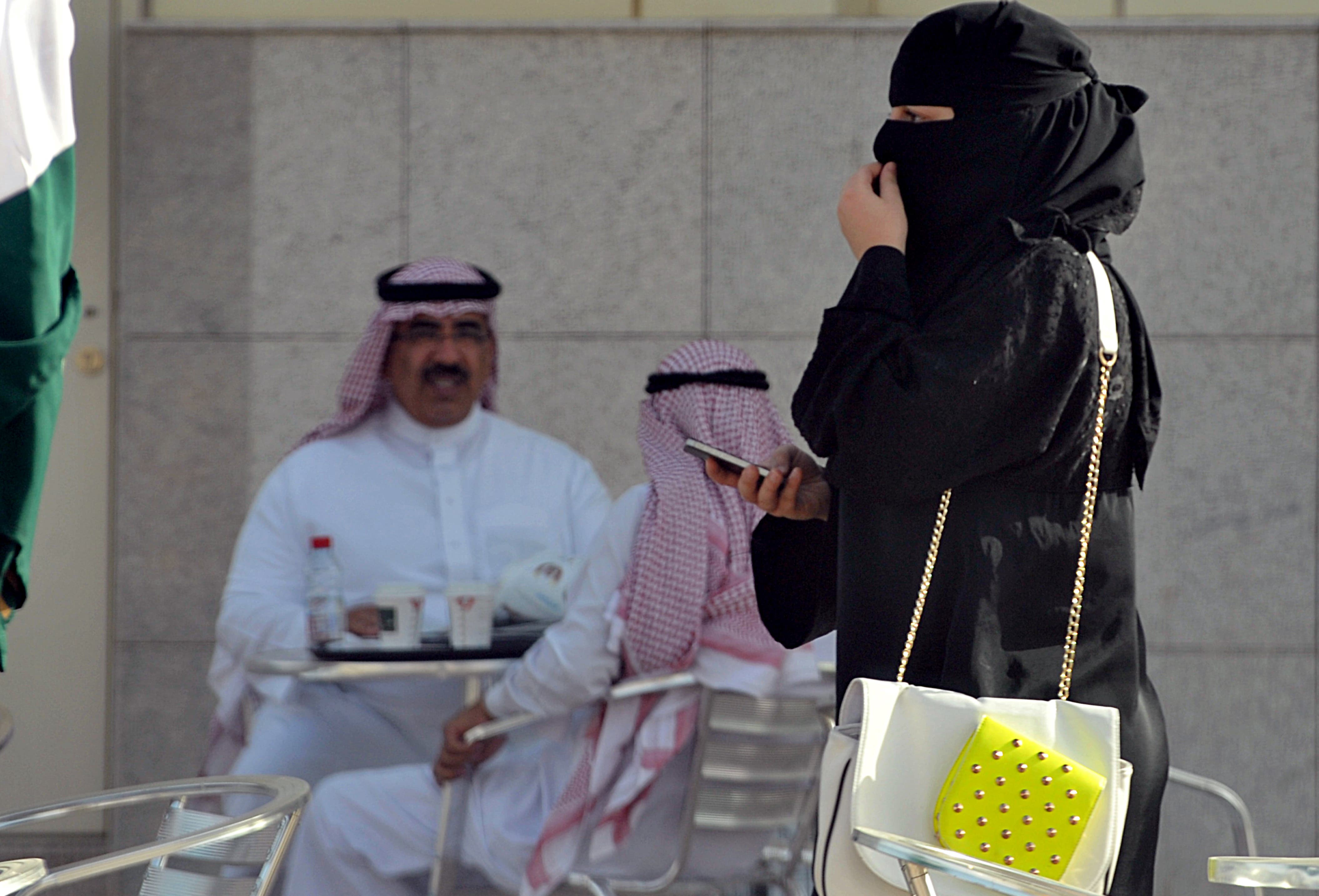 A Saudi woman holds her mobile as she walks through a coffee shop in the capital Riyadh on June 17, 2013. (Source: AFP/ FAYEZ NURELDINE)