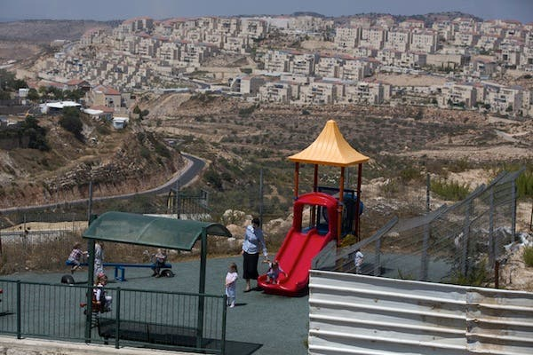 A Jewish woman looks after children at a play ground in the Jewish settlement of Beitar Elit at the Israeli occupied West Bank on August 12, 2013. (AFP)