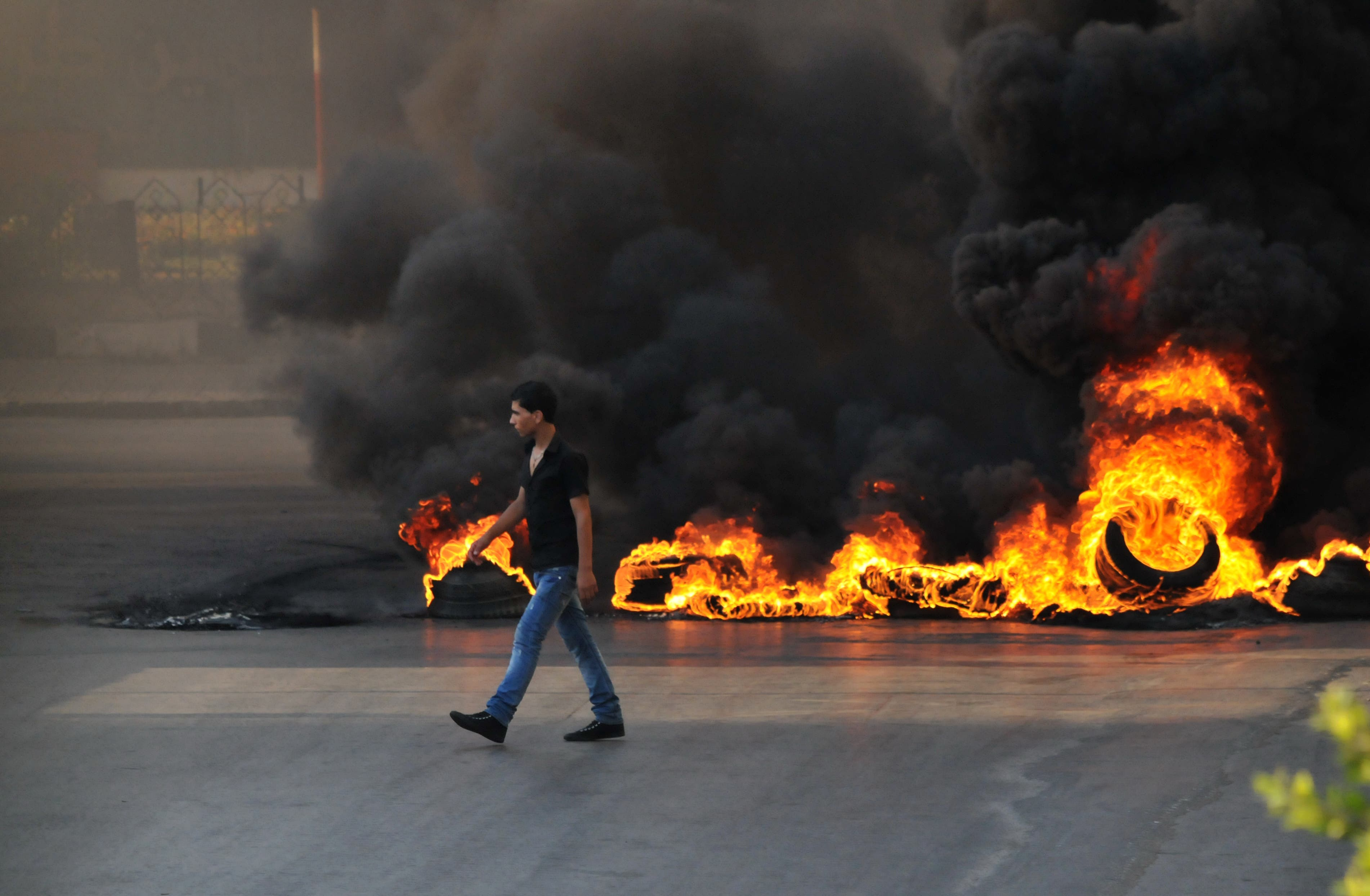 LEBANON, Tripoli : A youth walks past burning tires across a street in the northern city of Tripoli, on June 23, 2013, during protests in support of Sunni Muslim Sheikh Ahmad al-Assir whose supporters have clashed with the Lebanese army in the southern Lebanese city of Sidon. (Credit: AFP)