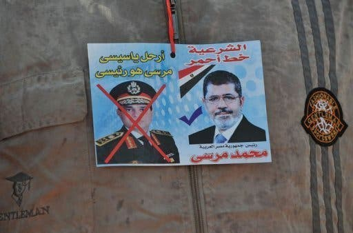 A sticker shows ousted president Mohamed Morsi (R) and army chief Abdel Fattah al-Sisi, in Cairo, July 24, 2013 (AFP)