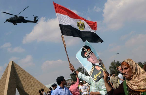 Egyptians waving the national flag and a portrait of Egyptian Defence Minister and Military Chief General Abdel Fattah al-Sisi in the district of Giza, on the outskirts of Cairo, on September 20, 2013. (AFP)