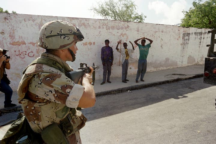 A U.S. Marine points a weapon at gunmen who are surrendering after a Marine patrol confiscated their weapons on December 21, 1992, near the Parliament building along Mogadishu's green line. (AFP)
