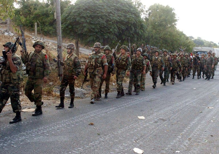 Syrian army soldiers walk on a road during an alleged pursuit of opposition fighters in the Latakia province, western Syria on August 8. (AFP/SANA)