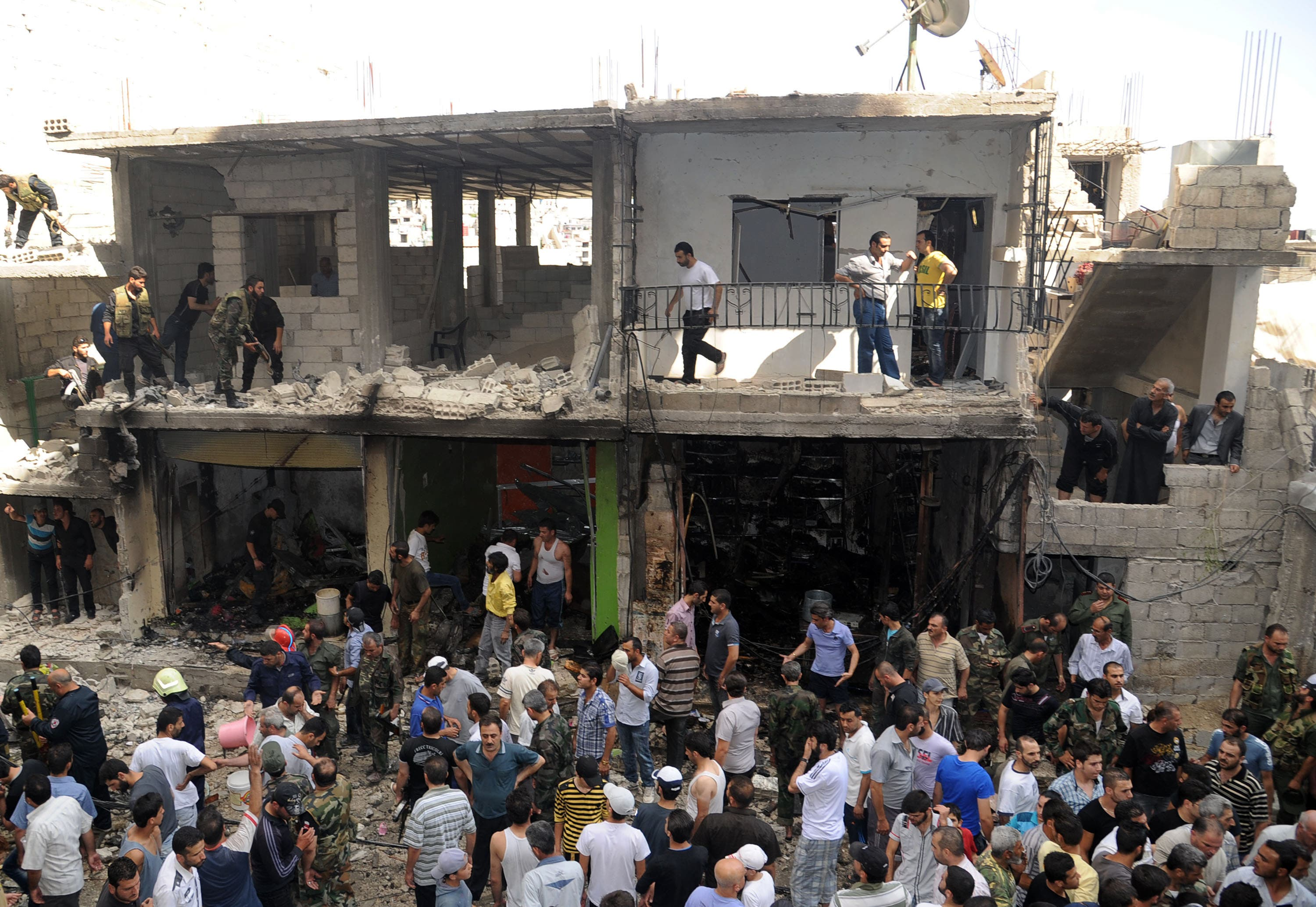 A handout picture released by the Syrian Arab News Agency (SANA) on June 23, 2013, shows civilians and security at the scene of a bombing in the Mazzeh 86 area of the Syrian capital Damascus. (Source: AFP/SANA)