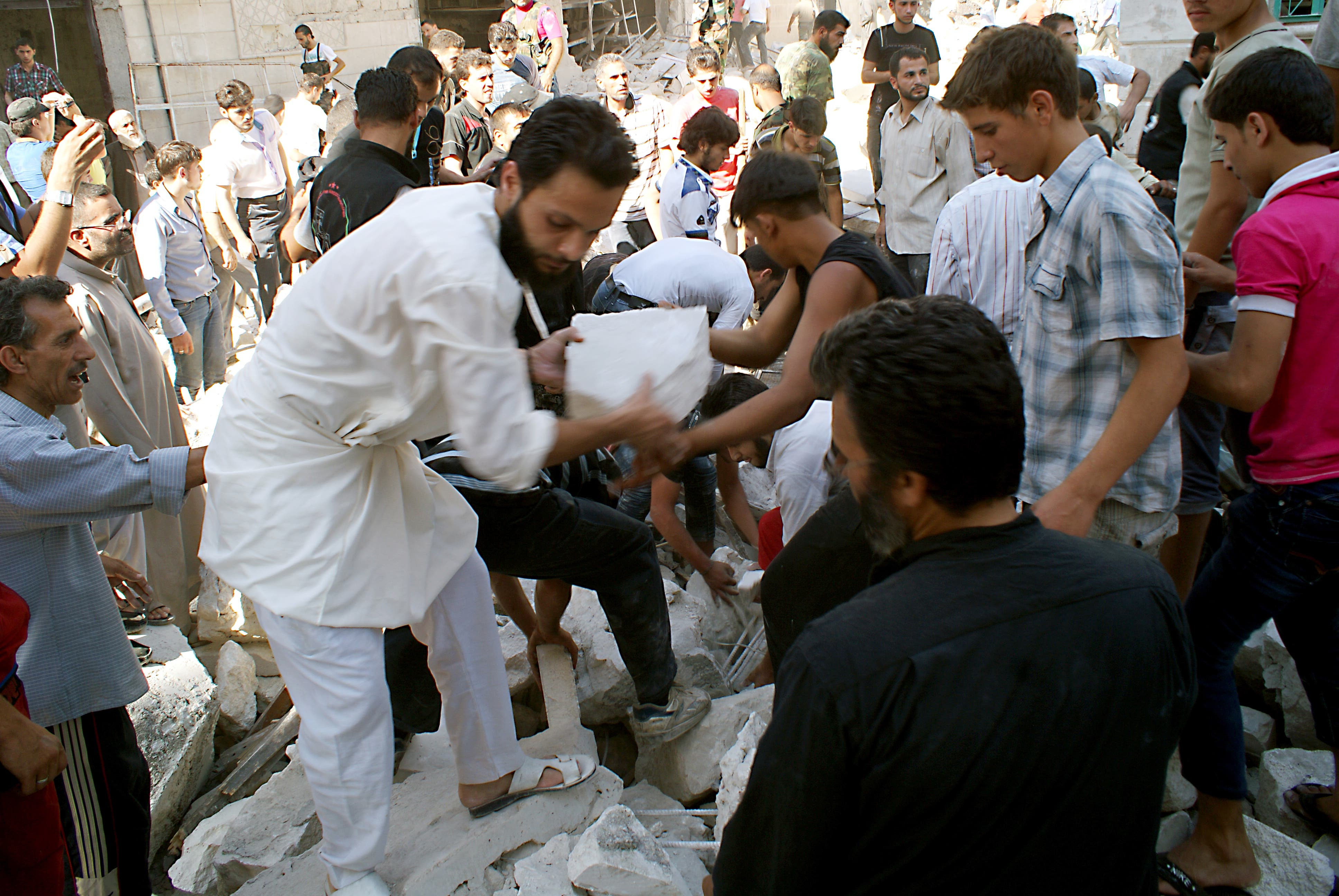 Rescuers and neighboors removes chunks of rubble from a partially collapsed building after a rocketed slammed into the side of a residential block located next to a mosque in the northern city of Aleppo on June 29, 2013. (Source: AFP/JALAL-ALHALABI)