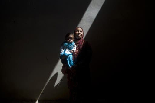Amina, a Syrian woman who fled the fighting in Aleppo, is photographed inside an abandoned building with her five-month-old sick daughter, Asma, on the outskirts of Saraqib, southwest of Aleppo, on September 9, 2013. According to the Red Cross, more than one million Syrians are going hungry. (AFP)