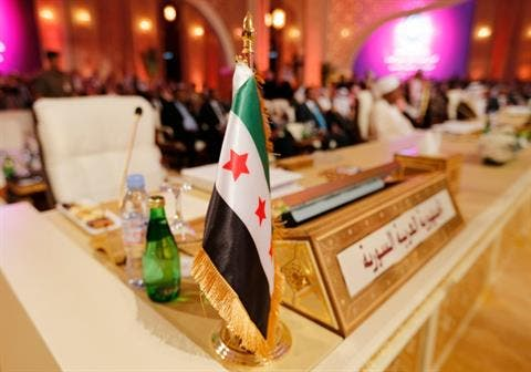 The flag of the Syrian opposition is shown at the seat of the delegation representing Syria at the Arab League summit in Doha in March. Image courtesy of The Daily Star
