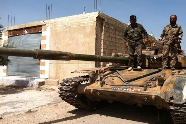 Syrian army soldiers standing on an army tank in the village of Buweida, north of Qusayr, in Syria's central Homs province on Friday. AFP photo