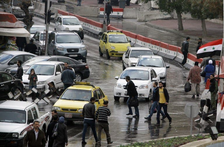 Syrians walk past cars in central Damascus on December 3, 2013 prior to a suicide attack in the Jebbeh district of the capital causing deaths and injuries, Syrian state television reported. (AFP)