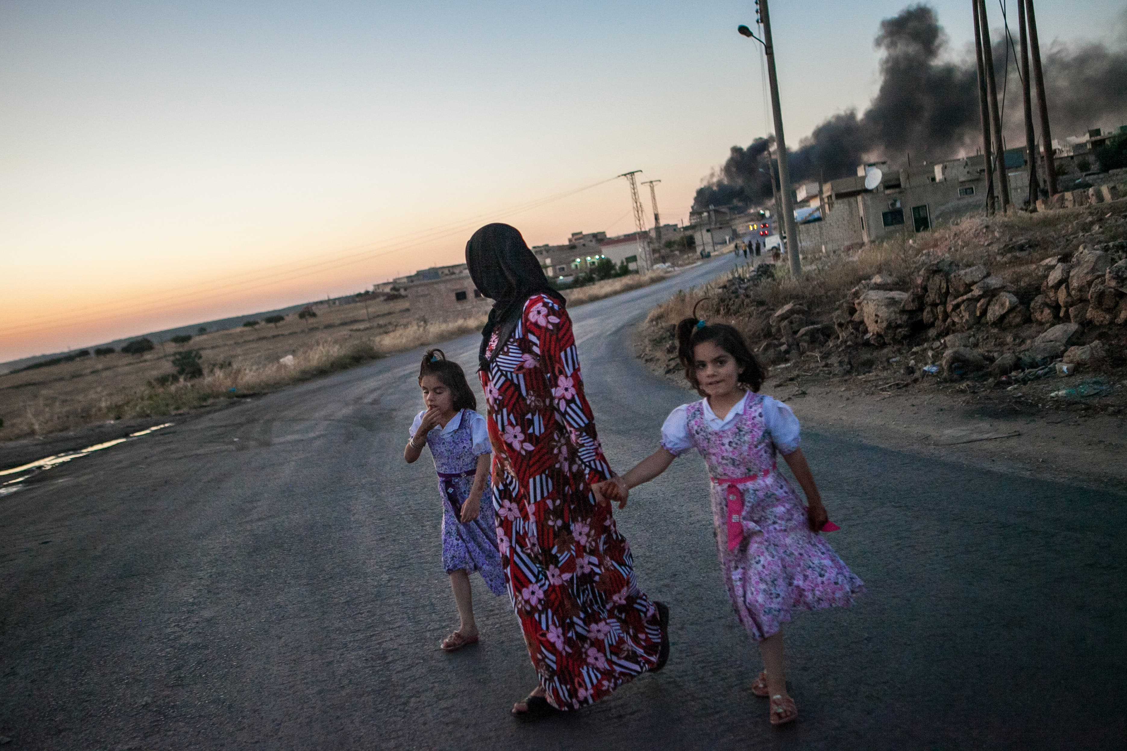 Syrian girls walk with their mother as she turns to look at smoke billowing from three shells dropped on the town of Al-Bara in the northwestern province of Idlib. (Source AFP/DANIEL LEAL-OLIVAS)