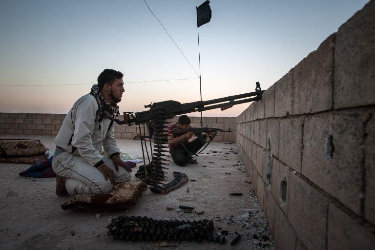 Rebel fighters takes aim at the location of Kurdish fighters in the outskirts of the northern Syrian city of Raqqa, on August 23, 2013. (AFP)