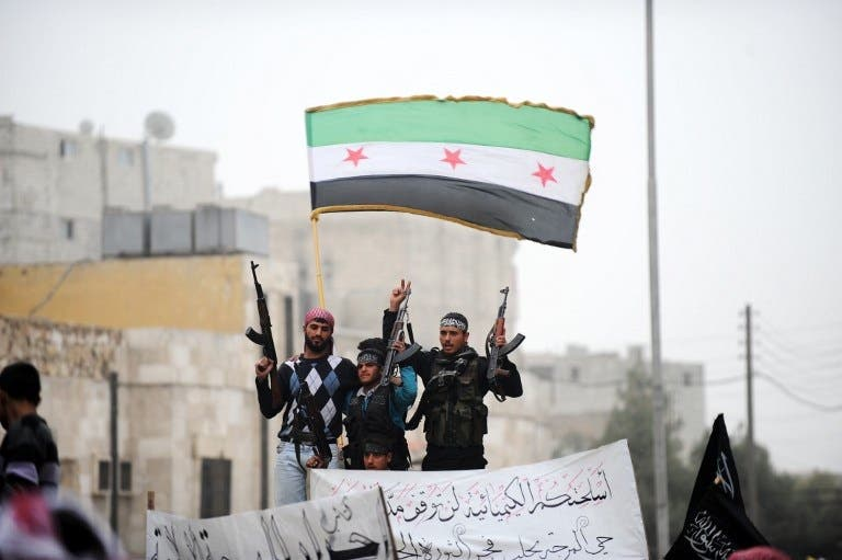 Syrian rebels raise their weapons under a pre-Baath Syrian flag currently used by the opposition during an anti-regime protest in the northern city of Aleppo. (AFP PHOTO/BULENT KILIC)