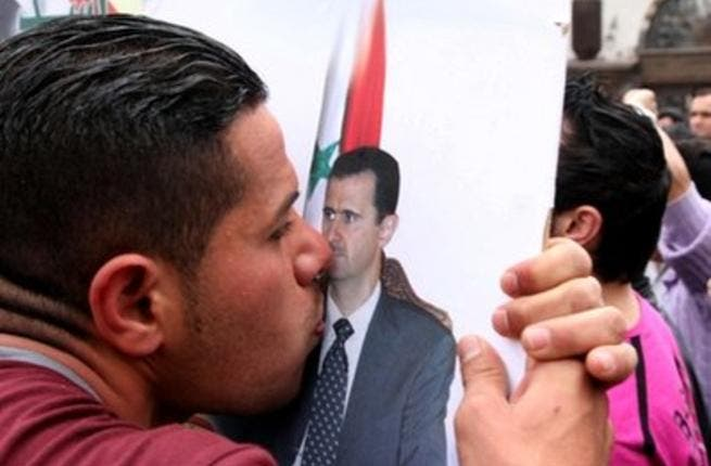 A pro-government supporter kisses a poster of Syrian President Bashar al-Assad.