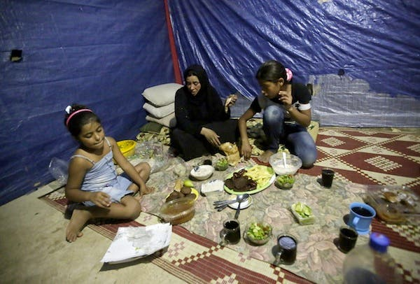 Fatima (C) a Syrian refugee widow, who lost her husband during the fighting in Homs, and her daughters have their Ramadan dinner in their makeshift room in a neighborhood of the Lebanese coastal city of Tripoli (AFP/JOSEPH EID)