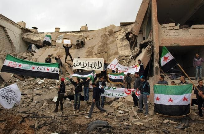 Syrians stand on the wreckage of a building, holding up placards and the Syrian pre-Baath flags during a demonstration against President Bashar Assad in Damascus last week. (AFP PHOTO/HO/SHAAM NEWS NETWORK)