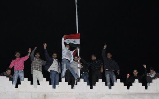 Syrians raise the national flag on the roof of the Qatar Embassy in Damascus on November 12, 2011.