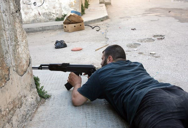 A fighter takes position in the al-Qobee neighborhood of the city of Tripoli, Lebanon on Monday. AFP Photo