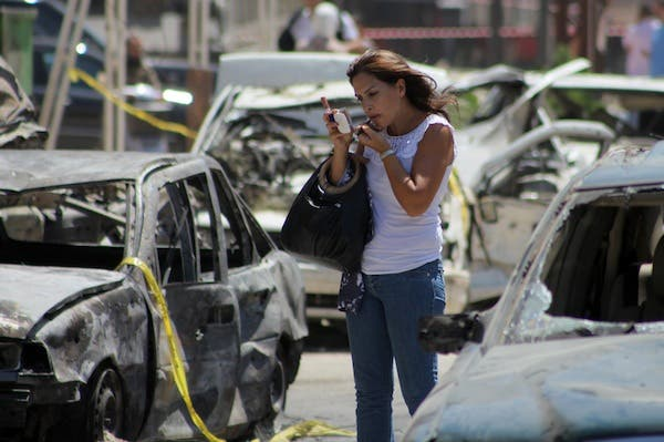 A woman adjusts her makeup amidst the wreckage following August's car bombs in Tripoli. (AFP/File)