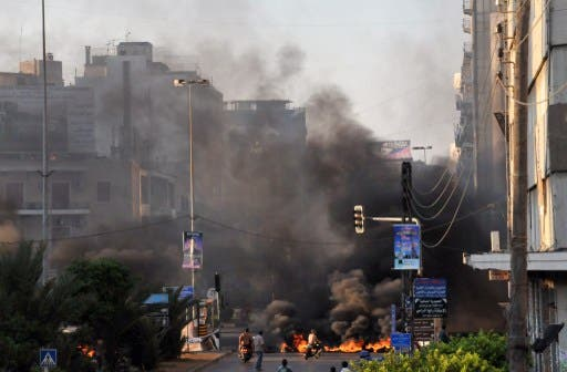 Black smoke acsends from burning tires laid across a street in the northern city of Tripoli on Sunday. (AFP)