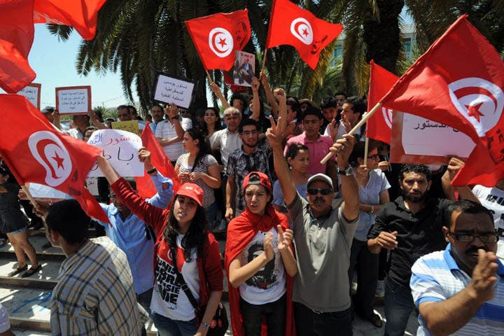 Tunisians shout slogans against the ruling Ennahda Party during a protest in front of the Constituent Assembly on July 1, 2013 in Tunis. Tunisia's National Assembly began debating for the first time the draft constitution, which has been criticised by opponents of the Islamist-led government and took far longer to promulgate than originally planned. (AFP PHOTO / FETHI BELAID)