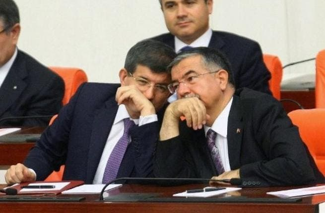 Turkish foreign minister, Ahmet Davutoglu cozies up to his defence minister during a debate on Syria