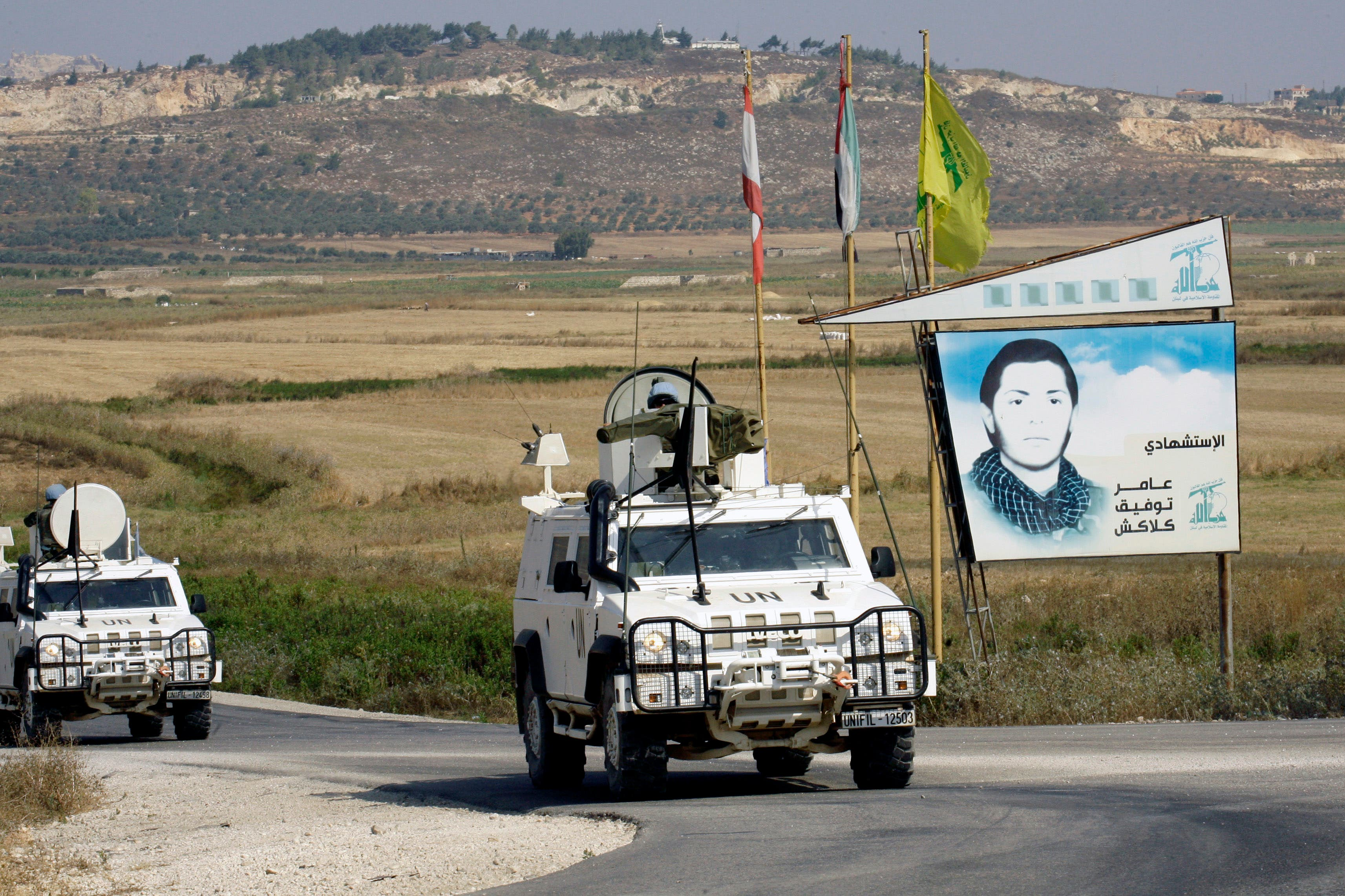 Spanish peacekeepers of the United Nations Interim Force in Lebanon (UNIFIL) patrol in their armoured vehicles near a placard of Hezbollah (AFP/MAHMOUD ZAYYAT)