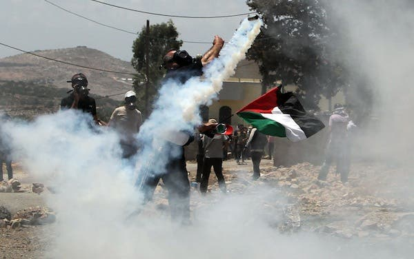 A Palestinian protester throws back a tear gas canister fired by Israeli security forces during clashes following a demonstration against the expropriation of Palestinian land by Israel in in the occupied West Bank on Friday. AFP Photo