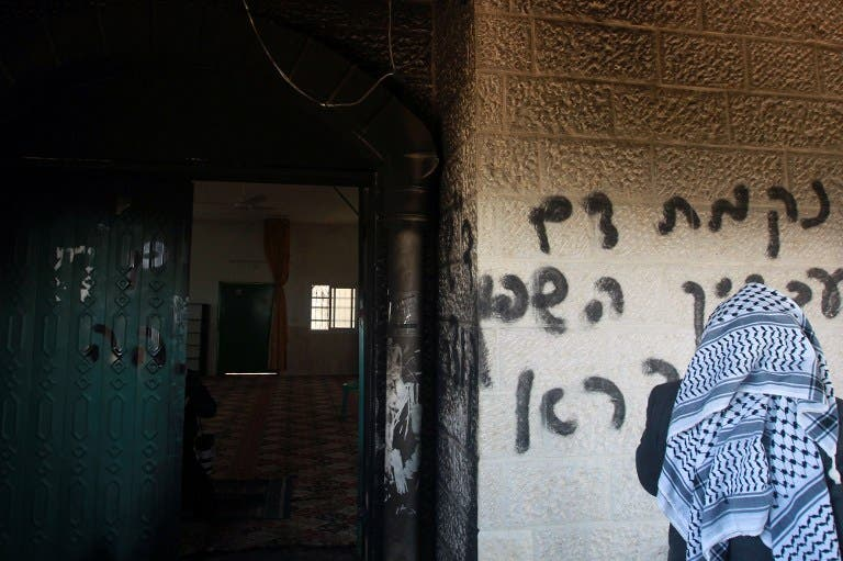 A Palestinian man looks at graffiti scrawled at the entrance to a mosque that reads in Hebrew,