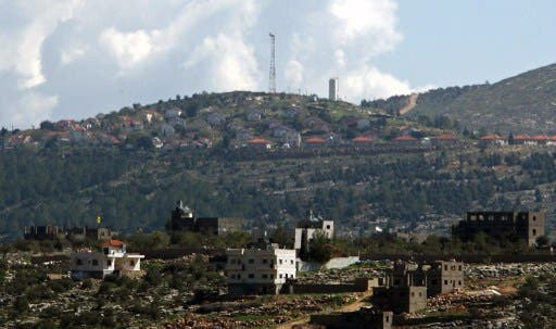 The general view of the Jewish settlement of Itamar (background) behind the West Bank village of Awarta. Israeli settlers are seeking approval for hundreds of homes in the northern West Bank. AFP photo