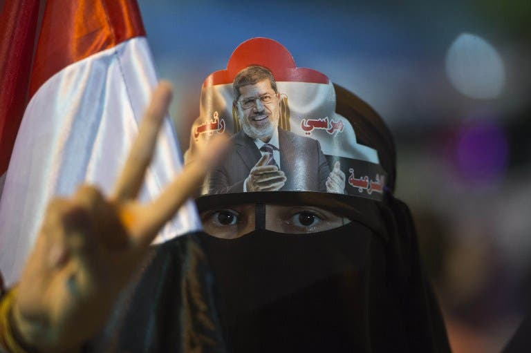A female supporter puts Egypt's deposed president Mohamed Morsi portrait on her head during sit in outside Rabaa al-Adawiya mosque in Cairo on August 1, 2013. (AFP)
