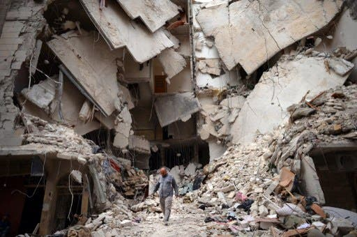 A Syrian man walks amid destruction in the northern Syrian city of Aleppo on Wednesday. (Photo:  AFP / DIMITAR DILKOFF)