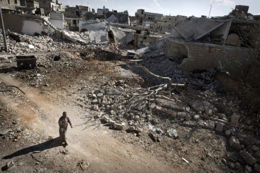 A man walks through a destroyed residential area of the Syrian city of Saraqib, southwest of Aleppo, on September 9, 2013, following repeated airstrikes by government forces. The Free Syrian Army have rejected the latest solution to the Syria crisis offered by the US and Russia. (AFP)