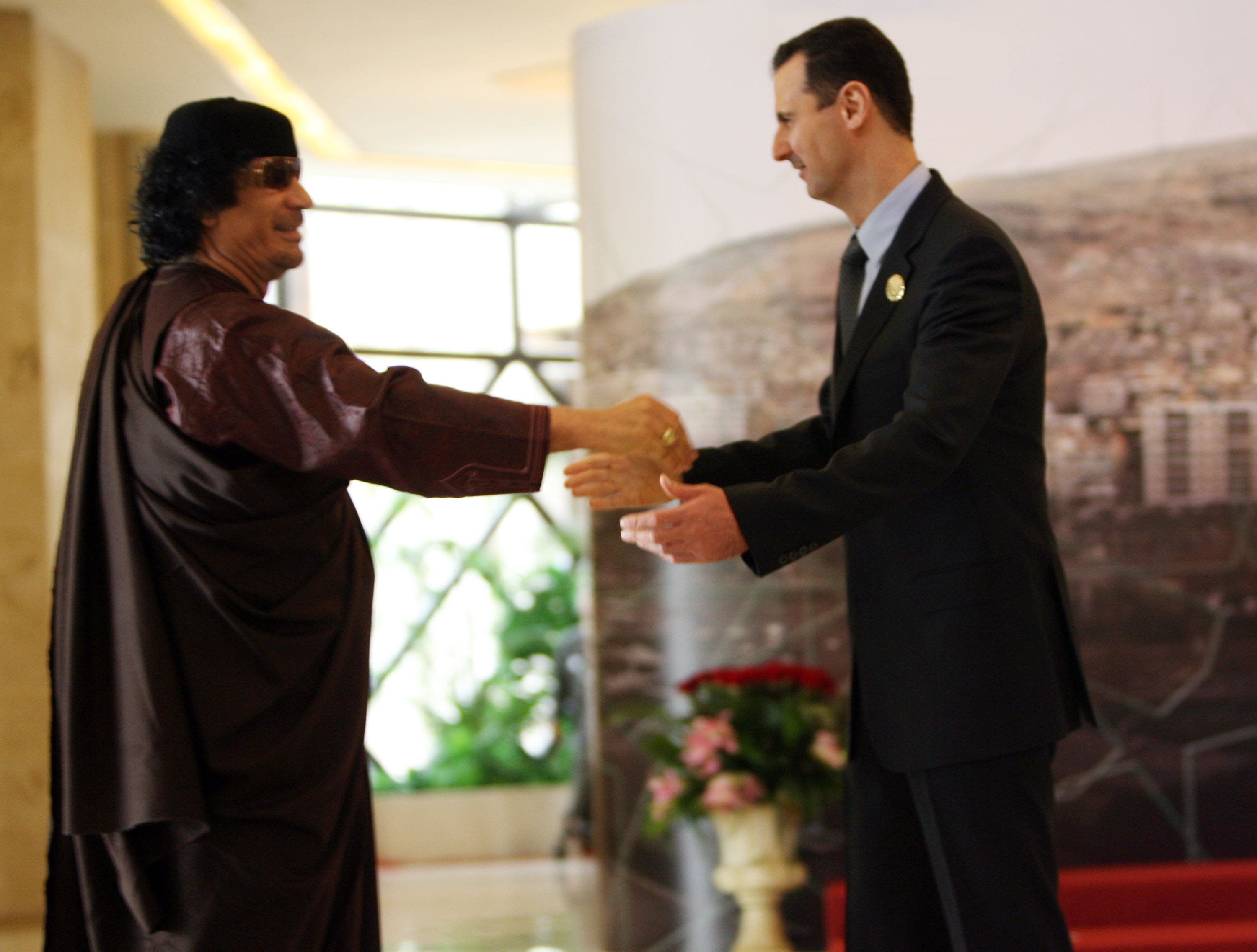 Both leaders Al-Assad and Gaddafi have seen better times. Here, they meet and greet at the Arab Summit at Damascus, 2008.