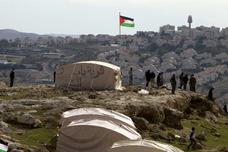 A Palestinian flag flutters as Palestinians, together with Israeli and foreign activists, stand near tents at the Bab al-Shams (Gate of the Sun) 'outpost' in the sensitive West Bank corridor east of Jerusalem on Saturday (Photo: AFP /AHMAD GHARABLI)