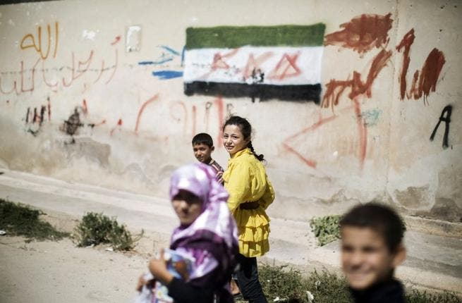 Children walk home from an improvised school in Azaz (AFP)