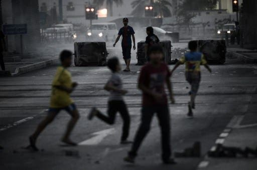 Bahraini boys run for cover during clashes following an anti-regime rally in support of political activists held in prison in the village of Jidhafs, west of Manama on Monday. (Photo:  AFP /MOHAMMED AL-SHAIKH) - Photo used for illustrative purposes -