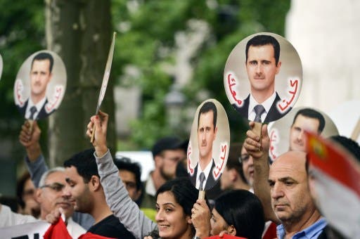 Demonstrators raise portraits of Syrian President Bashar Assad on September 8, 2013 in Brussels to protest against a potential military strike against Syria. (AFP)