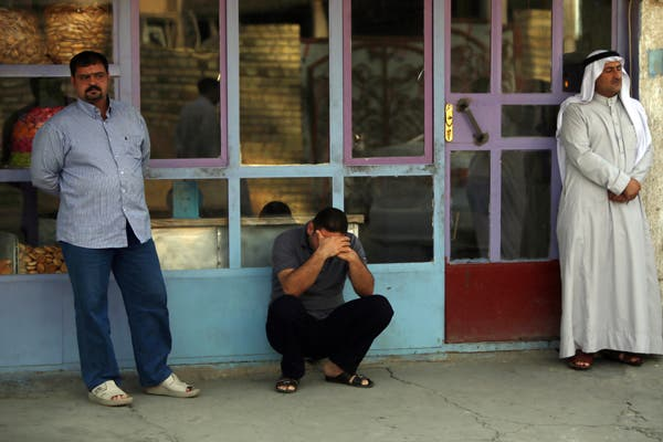 Iraqi men mourn family members on July 14, after an attack the day before (source: AFP / AHMAD AL-RUBAYE)