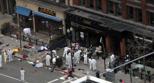 Investigators in white jumpsuits work the crime scene on Boylston Street following Monday's bomb attack at the Boston Marathon. (Photo: Darren McCollester/Getty Images/AFP)