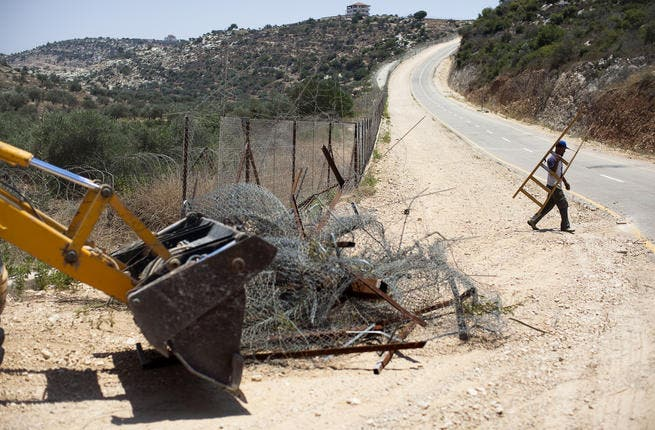 Israeli bulldozers usually seen by Palestinians on the 'wrong' side of the fence. This time, they're starting to break down the right barriers. Some say it's not enough to pull down just 'some' of the Wall dividing Palestine.