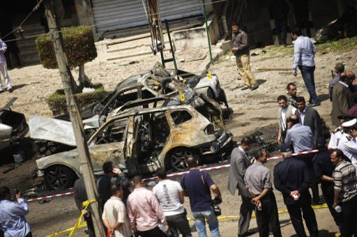 gyptians gather at the site of a bomb that targeted the convoy of the Egyptian Interior Minister Mohammed Ibrahim in Cairo on September 5, 2013. (AFP)