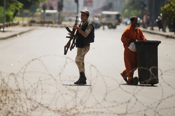 An Egyptian army soldier holds his rifle as he walks by a street cleaner behind a barbed wire checkpoint on a street in Cairo on August 23, 2013. (AFP)
