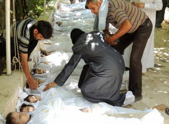 A woman mourns over a body wrapped in shrouds laid out in a line on the ground with other victims which Syrian rebels claim were killed in a toxic gas attack by pro-government forces in eastern Ghouta, on the outskirts of Damascus on August 21, 2013. (AFP/HO/Shaams News Network)