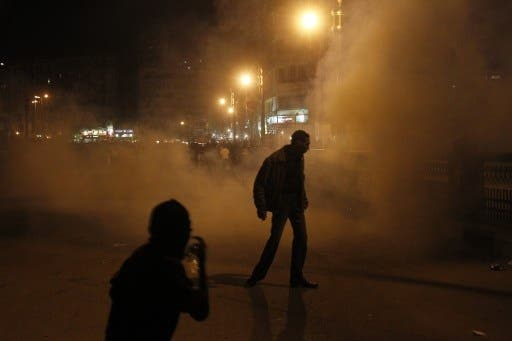 Egyptian protesters walk away after riot police used tear gas during a protest in Tahrir Square on January 24, 2012 in Cairo. (Photo: MOHAMMED ABED / AFP)