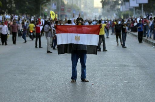 An Egyptian protestor holds his national flag during clashes between supporters of the Muslim Brotherhood and Egypt's ousted president Mohamed Morsi and security forces, in Cairo, on August 30, 2013. (AFP)