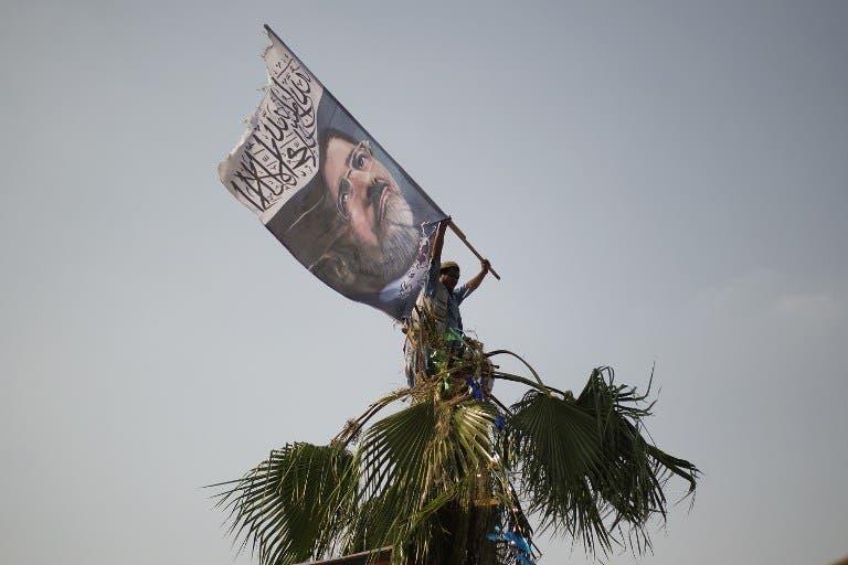 A man waves a flag picturing ousted president Mohamed Morsi on July 9, 2013. (source: GIANLUIGI GUERCIA / AFP)