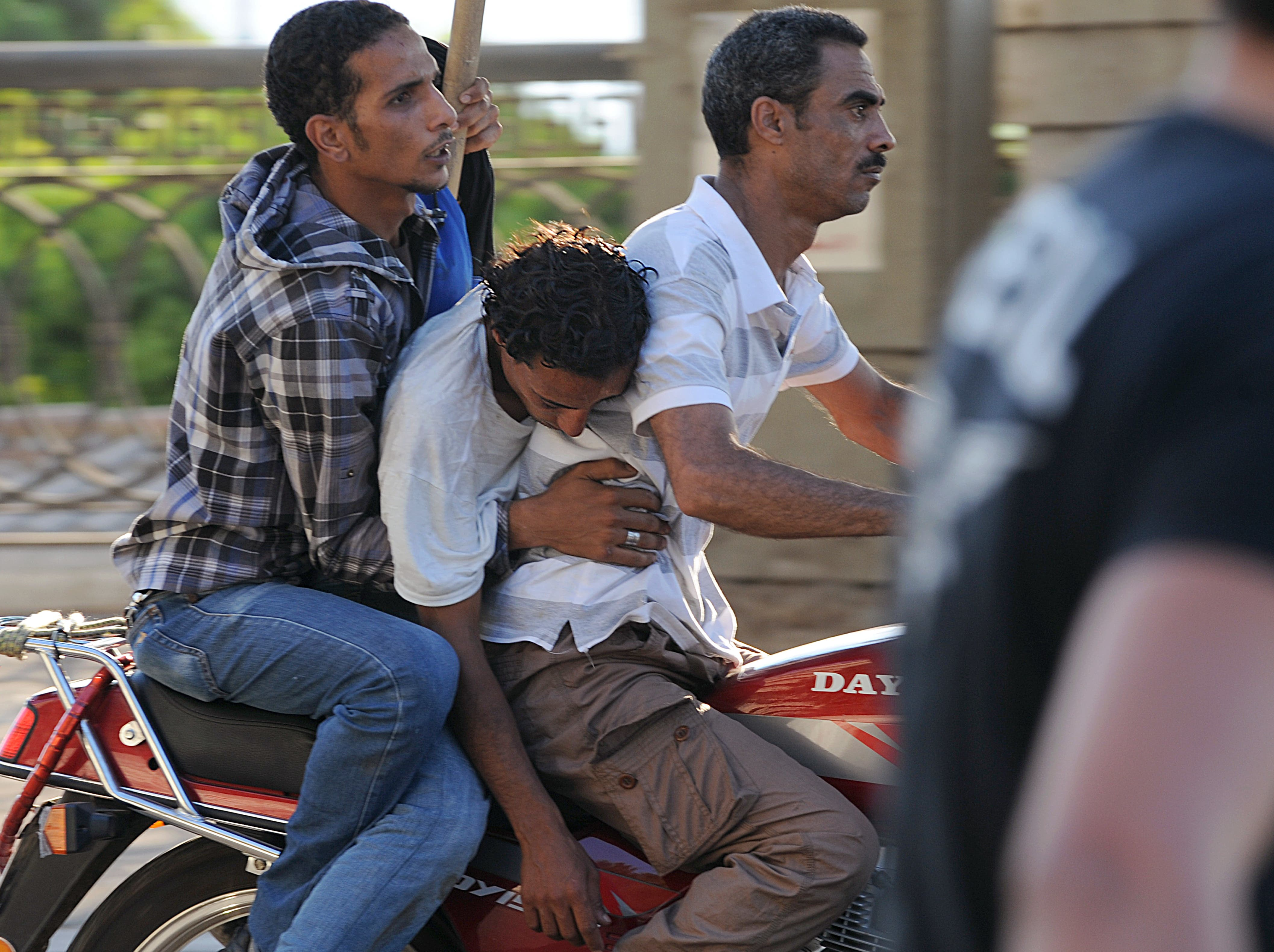 Army supporters evacuate an injured man after clashes with Morsi supporters on July 22. (AFP / FAYEZ NURELDINE)